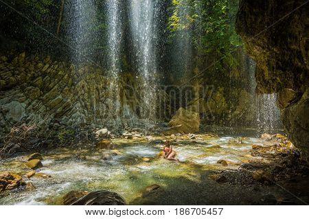 Image of young girl in waterfall near Panta Vrexei in Evritania Greece