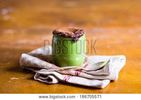 Chocolate souffle in a small cup on a wooden table, selective focus