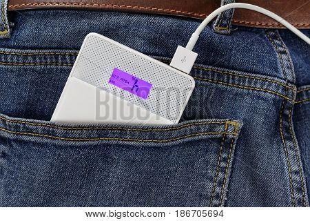 Power Bank With Connection Usb Cable In The Back Pocket Of The Jeans Closeup