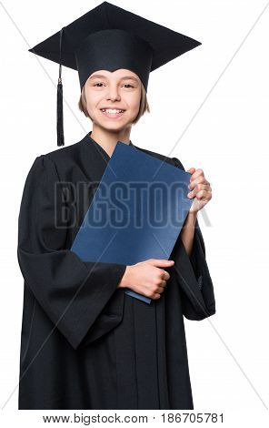 Portrait of a graduate little girl student in a black graduation gown with hat, holding certificate - isolated on white background. Child back to school and educational concept.
