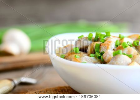 Roasted mushrooms slices with sour cream and fresh green onions in a bowl. Healthy vegetarian meal. Homemade wholesome mushrooms recipe. Fresh mushrooms, green onions, fork on vintage wooden table