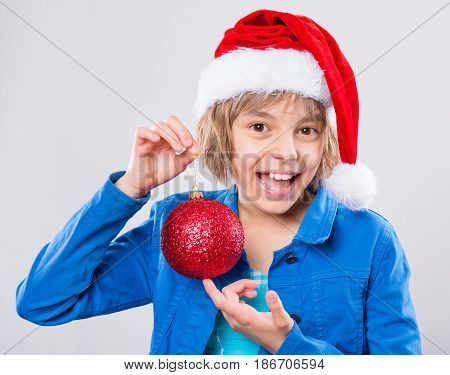 Emotional portrait of attractive caucasian little girl wearing Santa Claus red hat. Funny cute smiling child 10 year old with beautiful Christmas ball on gray background. Winter holiday concept.