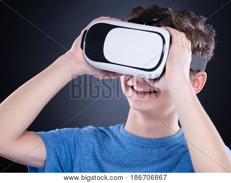 Happy teen boy wearing virtual reality goggles watching movies or playing video games. Cheerful smiling teenager looking in VR glasses. Funny child experiencing 3D gadget technology - close up.