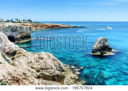 Rocky coast, the sea and a floating boat. Cyprus