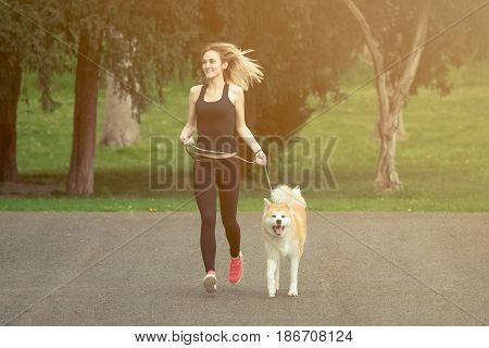 Woman and dog jogging in the park. Healthy lifestyle and pets concepts.