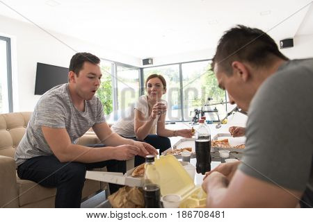 a group of young people cheerfully spending time while eating pizza in their luxury home villa