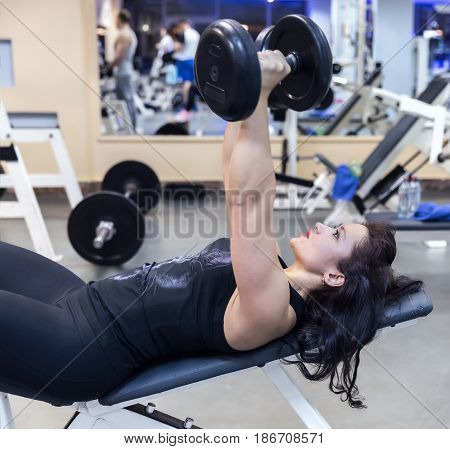 Sporty girl lying on the bench with dumbbells in her hands in the gym. Build muscles of the arms and chest. Side view. Concept of healthy lifestyle