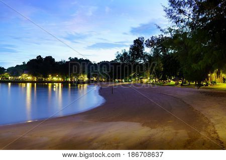 Sandy beach at night with lights, houses, and trees visible in teh distance. The blue evening sky give an overall holiday vacation feel