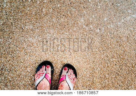 Girl's feet with henna tattoos and sandles. She is standing on a sandy beach probably on a honeymoon vacation