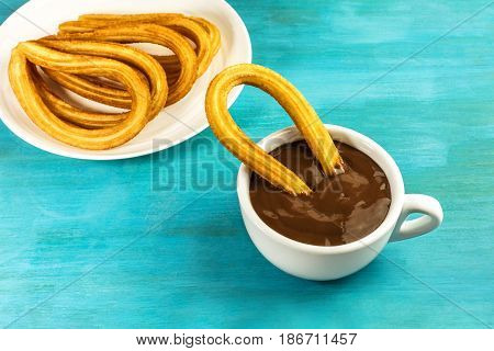 A plate of churros, traditional Spanish, especially Madrid, dessert, particularly for Sunday breakfast, with a cup of hot chocolate, on a turquoise table with a place for text