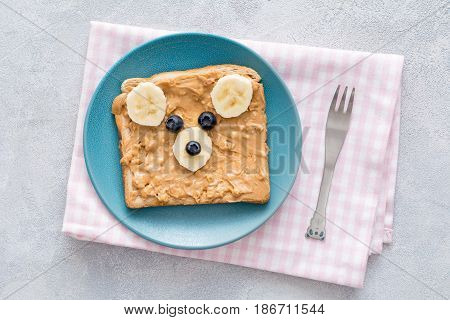 Teddy bear toast for kids. Crunchy peanut butter, banana and blueberry toast with cute teddy bear face on a blue plate over pink checkered textile. Top view. Concept of kids breakfast, food for kids