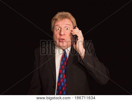 Shocking news. Surprised senior man in formalwear holding mobile phone and standing against black studio background