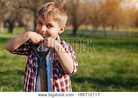 Charming helpmeet. Adorable hazel-eyed child wearing a plaid shirt leaning on a shovel and looking into the camera