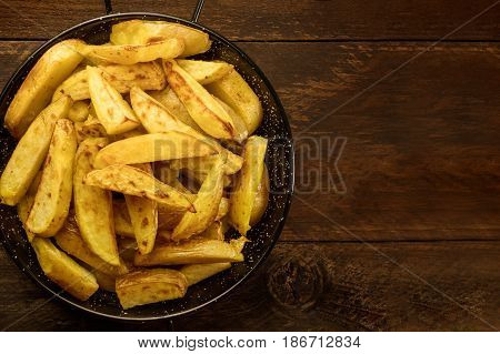 A photo of crunchy potatoes, roasted with salt and garlic, in a skillet, shot from above on a dark wooden background with a place for text
