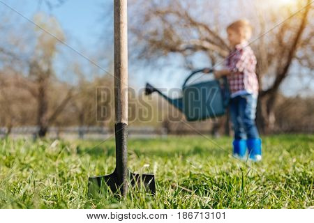 Gardening practice. A shovel digging soil with a little boy on the background watering a vernal lawn with a green pouring pot