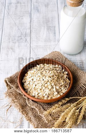 Organic oat flakes, rolled oats in brown ceramic bowl, wheat ears and bottle of milk on rustic white table. Vertical image with copy space