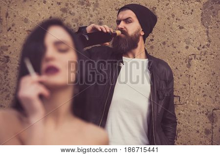 Bearded Brutal Man Drinking And Blurred Sexy Girl Smoking