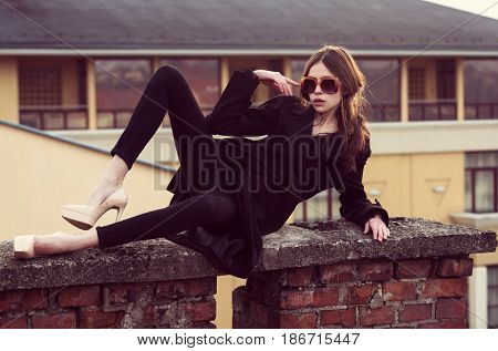 woman. Adorable fashionable woman or cute girl in vintage sunglasses stylish black coat and elegant beige shoes on high heels lying on red brick fence outdoors on urban background. Modern fashion and style