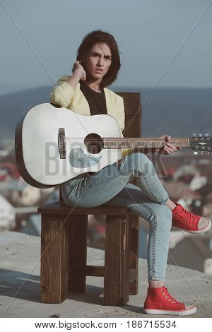 singer. Pretty girl guitarist or cute woman musician with brunette hair playing guitar musical instrument on wooden chair on idyllic sunny summer day outdoors on blue sky. Music and entertainment