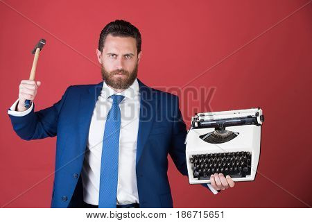 technology. business man in blue suit and tie with typewriter businessman hold hammer on red background failure and challenge crisis and problem stress and overtime