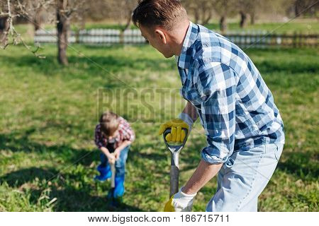 Home-gardeners in action. Focus on a mature man looking at his little son, both wearing plaid shirt and digging the soil in a family garden