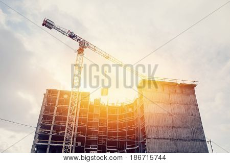 Crane puts a concrete slab on the slab for building a house with workers on top. The concept of erecting multi-storey apartments. Sunny highlight.