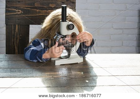 Educational Concept, Boy Student Studying At Workplace With Microscope
