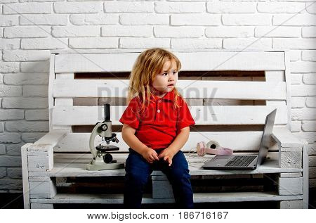 Student Boy With Laptop And Microscope And Headset On Bench