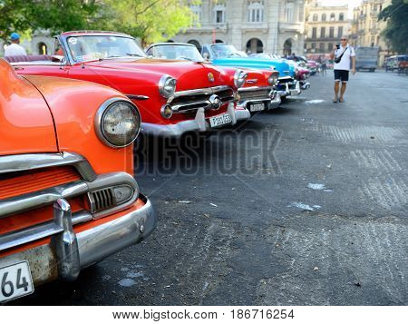 HAVANA CUBA - 07 DECEMBER 2016: Old American cars serving as taxis for tourists in order to go on a tour of old Havana standing in the Central Park in the heart of Havana Cuba