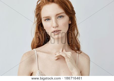 Young beautiful redhead girl with freckles looking at camera. Copy space. Isolated on white background.