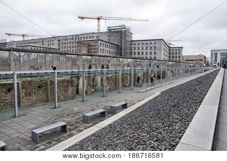 BERLIN GERMANY - APRIL 7: Berlin wall and ruins of SS headquarters in museum Topography of Terror and yellow sightseeing bus on April 7 2017 in Berlin