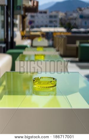 An empty table with an ashtray in a street restaurant. Focus on the foreground.