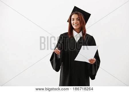 Happy cheerful african girl graduate smiling holding test over white background. Copy space.