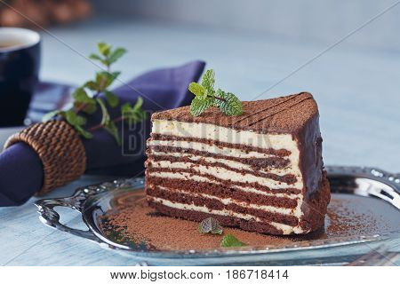 Slice of delicious chocolate cake on silver plate with fresh mint on light blue wooden table background.