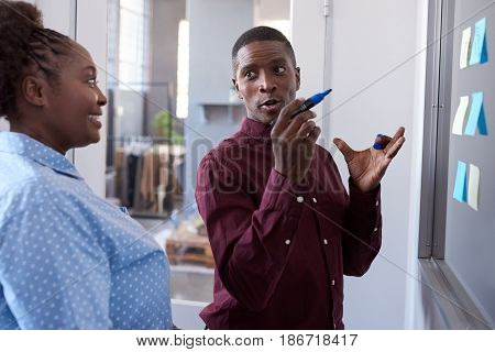 Two casually dressed African coworkers strategizing together on a glass wall with sticky notes while standing in a modern office
