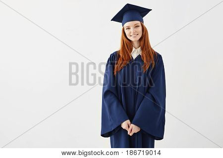 Happy redhead female graduate smiling looking at camera over white background. Copy space.