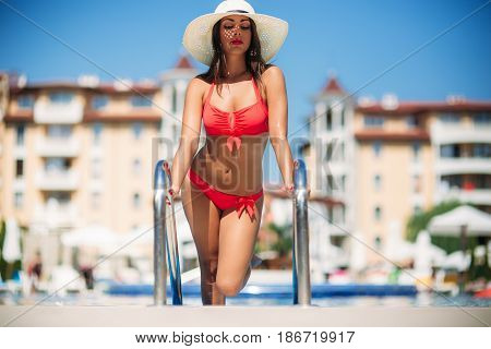 A beautiful girl in a pink bathing suit sunbathing by the swimming pool .Sunny weather. Summer.