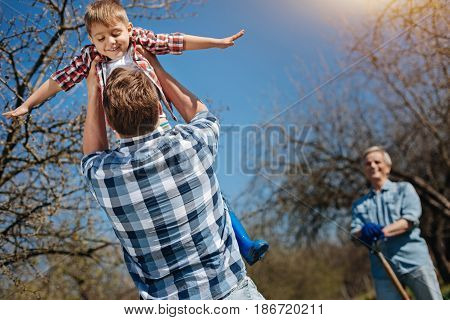 Fly me to the moon. Father and son having fun outdoors as father holding an excited kid up over head while a smiling grandad watching them