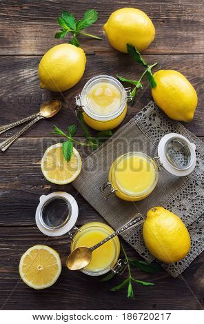 Fresh homemade lemon curd in glass jars on rustic wooden background. Top view.