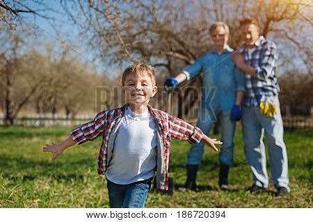 Catch me. Cute little child with outspread hands running around in a garden and rejoicing the time spent with his father and granddad