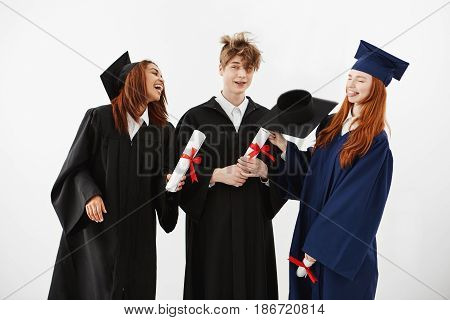 Three cheerful graduates in caps and mantles smiling speaking fooling holding diplomas over white background.