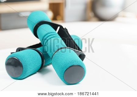 Fitness at home concept, a pair of green dumbbells in the foreground and an fitness ball and in the background in fitness in living room.