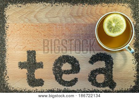 On the Board is a mug with black tea. In a mug slice of yellow lemon. On the brown Board from the scattered tea leaves of black tea small leaf lined with the letters of the word tea.