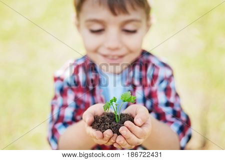 Saving mother nature. Adorable little boy in a plaid shirt smiling and looking at the plant in his hands