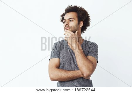 Uncertain african man thinking looking in side over white wall, deciding whether to buy some gadgets online or a student trying to remember a party. Copy space.