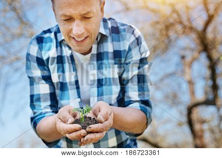 Caring about environment. Mature man wearing plaid shirt holding a sprouting plant in a soil surface, looking at it and smiling