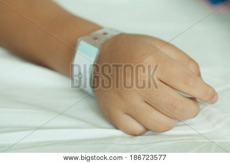 Hands of littel boy and Wristband barcode in hospital bed