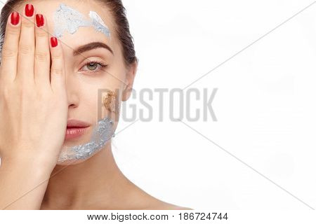 Woman with cosmetics looking at camera and closing half of face isolated on white.