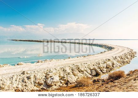 View of Dead Sea coastline with white beach made salt at sunny day in Ein Bokek, Israel. White mineral salt shore at Dead sea, Israel landscape.
