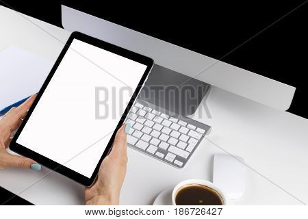 Woman hands holding tablet computer with isolated screen and cup of coffee. Business workplace with computer and wireless mouse and keyboard.business objects